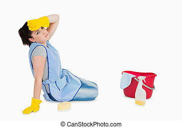 Exhausted woman cleaning the floor