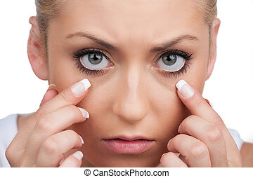 Exhausted woman. Close-up of exhausted young woman looking at camera while isolated on white