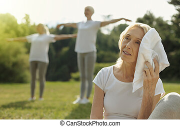 Exhausted woman wiping forehead after workout outdoors