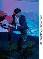 businessman sitting on bed in dark room