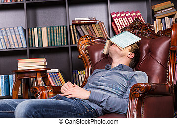 Exhausted young man sleeping in a library