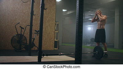 Exhausted young men resting after intensive workout in gym. Exhausted male athlete is resting after training. Drops of water is draining from his face, workout in gym. High quality 4k footage