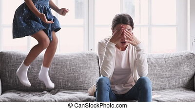 Exhausted young mother tired of hyperactive noisy kid daughter. Tired adult parent mum having headache feel fatigue from noisy child jump on sofa at home. Children adhd hyperactivity disorder concept