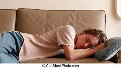 Exhausted young sleepy woman falls down on sofa. Apathetic tired lazy lady sleeping on couch at home alone