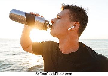 Exhausted young sportsman in earphones
