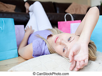 Exhausted young woman after shopping lying on the floor