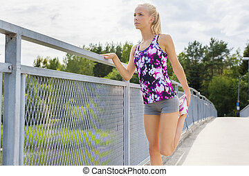Exhausted young woman stretching after running