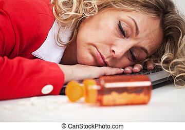 Exhaustion - woman asleep on computer keyboard with pills in foreground