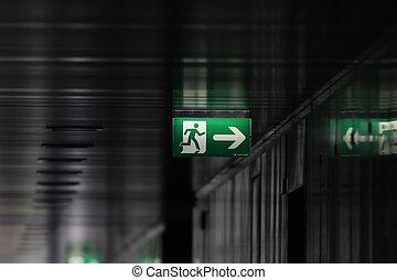 Green exit sign along a black aisle