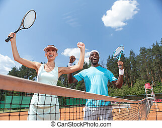 Exited couple is rejoicing at success during tennis match