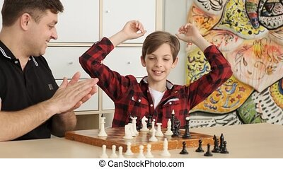 Exited emotional boy is winning his Dad in chess slow motion...
