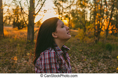 Exited girl in the woods at sunset