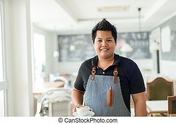 exitoso, propietario de la pequeña empresa, posición, con, un, taza de café, latte.