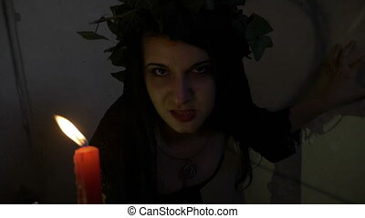 Exorcism of witch with evil sneer possessed by demon dressed in black snarling and holding a candle in her hand