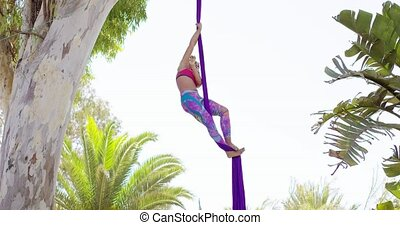 Exotic acrobatic dancer working out on silk ribbon