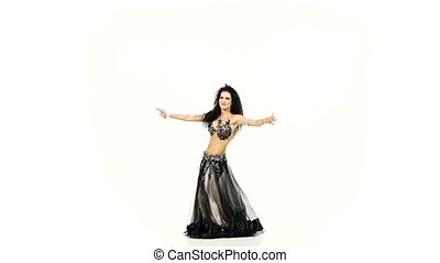 Exotic beautiful belly dancer with long dark hair shaking her hips, on white, slow motion