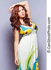 Exotic beauty in long sleeveless dress