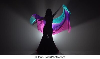 Beautiful exotic belly dancer girl continue dance uses fans. Sihouette . Black smoke background. Slow motion
