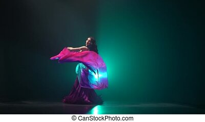 Beautiful exotic belly dancer girl continue dance uses fans. Smoke background