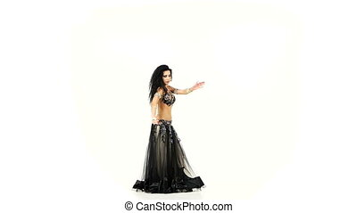 Exotic belly dancer with long dark hair shaking her hips, on white, slow motion