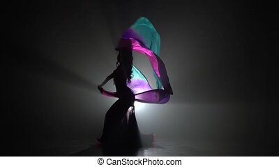 Beautiful exotic belly dancer woman continue dance uses fans. Sihouette . Black smoke background