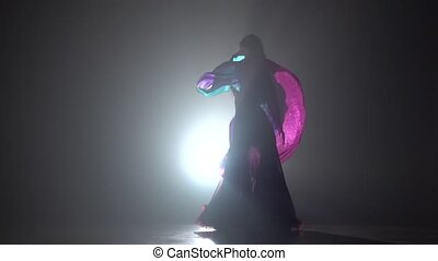Beautiful exotic belly dancer woman continue dance uses fans. Sihouette . Black smoke background. Slow motion