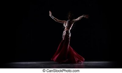 Exotic belly dancer woman shaking her hips in dress. Black...