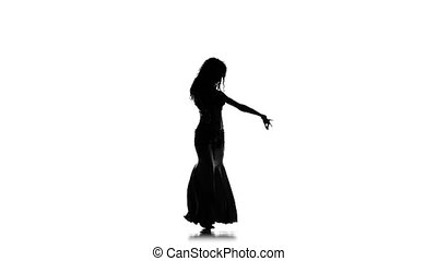 Exotic belly dancer woman, shaking her hips, on white, slow motion, silhouette