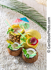 Exotic drinks in fresh fruits with cocktail umbrellas