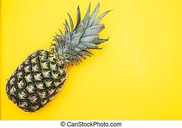Exotic fruit of pineapple on a yellow background. Copy space