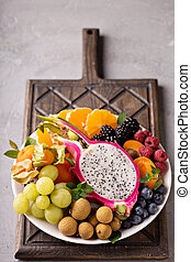 Exotic fruits platter with grapes, dragon fruit, longan and...