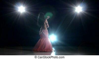 Exotic long-haired belly dancer girl dancing exotic dance movement on black, back light