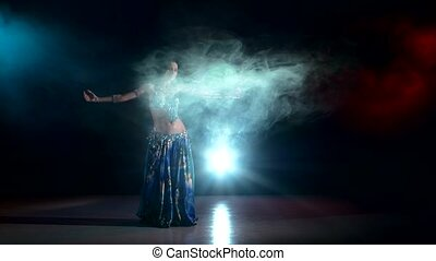 Exotic long-haired belly dancer girl dancing exotic dance movement on black, smoke, back light