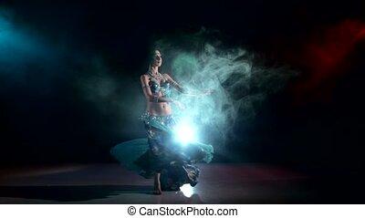 Exotic long-haired belly dancer girl starting dancing exotic dance movement on black, smoke, back light