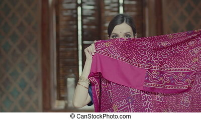 Exotic shy indian woman covering face with sari - Modest...