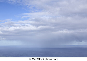 expanse of sea and sky with blue part and clouds with distant rain storm