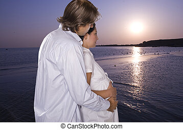 Expectant couple on beach looking at sunrise - Lovely young...