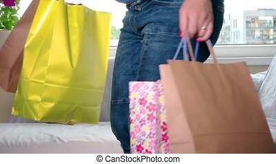 Expectant female with shopping bags looking at baby clothes sitting on sofa