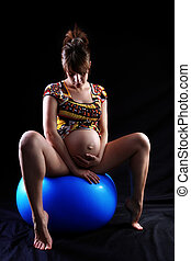 expectant mother 40 weeks sitting at big blue ball