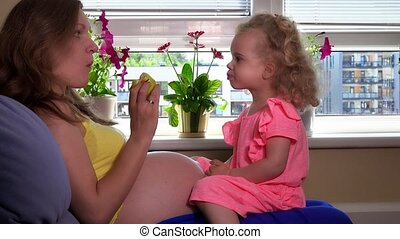 expectant mother and her cute daughter eating apple fruit at...