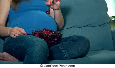 expectant mother hands caress huge tummy and eat cherry...