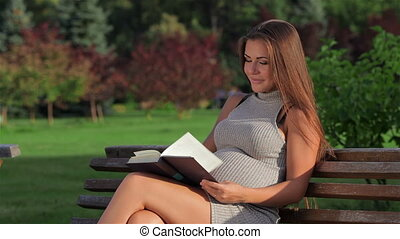 Expectant mother is reading a book