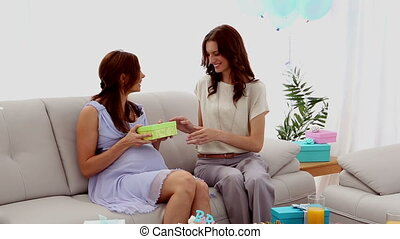 Expectant mother opening a present from friend at home at...