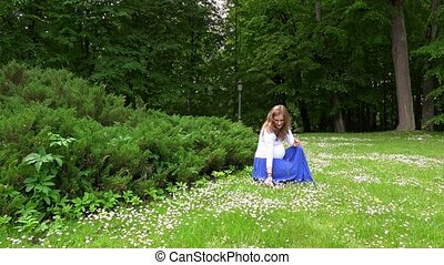 expectant mother picking daisy flowers in park meadow....