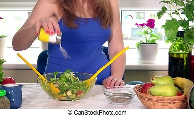expectant mother pour salt and mix ecologic vegetables salad...