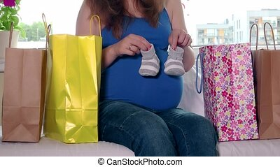 Expectant mother sitting between shopping bags and stroking...
