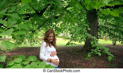expectant mother standing under tree brunches and stoke her...