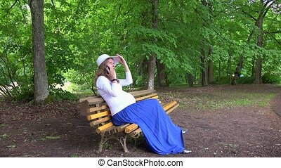 expectant mother talk on phone while sitting on park bench...