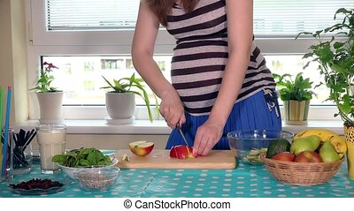 Expectant mother tummy and hands slicing pear fruit on cutting board