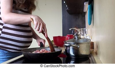 Expectant mother woman preparing meat in cooking pan. Big female belly